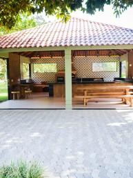 Área de socialização coberta com cadeiras e mesas.